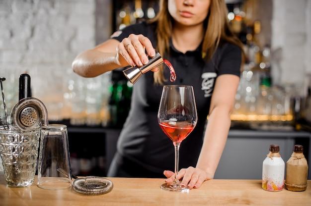 Белокурая барменша делает коктейль у барной стойки с использованием барного оборудования