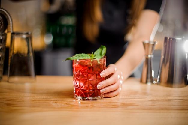 Барменша держит в руках хрустальный бокал с коктейлем красного цвета