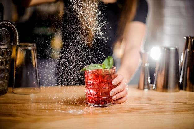 Барменша заканчивает приготовление коктейля, добавляя немного сахарной пудры