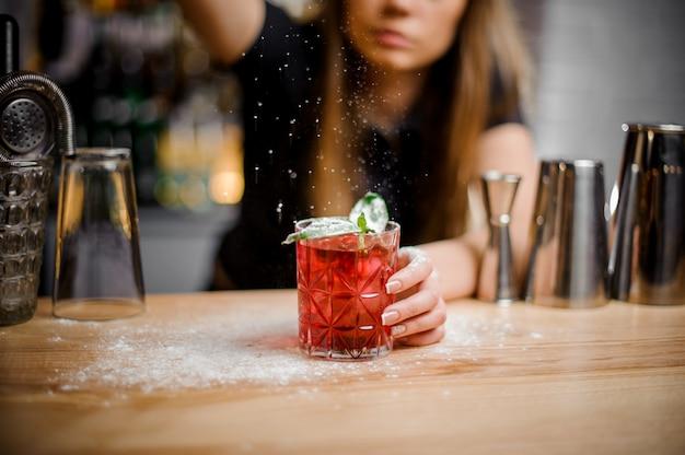 Симпатичная бариста заканчивает приготовление алкогольного коктейля с мятными листьями сахарной пудры