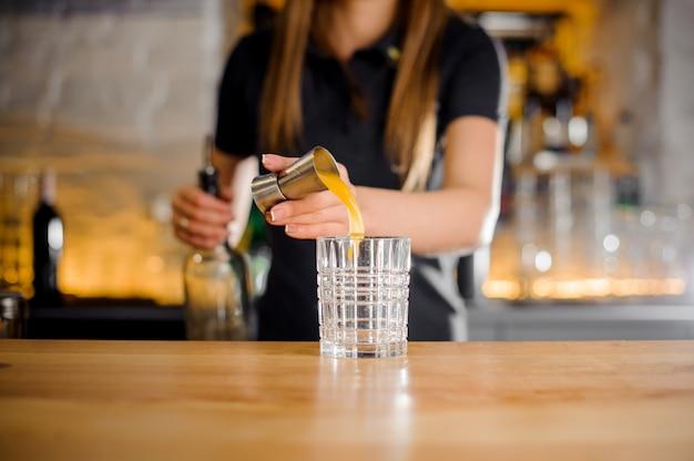 Бариста начинает готовить алкогольный коктейль с апельсиновым соком