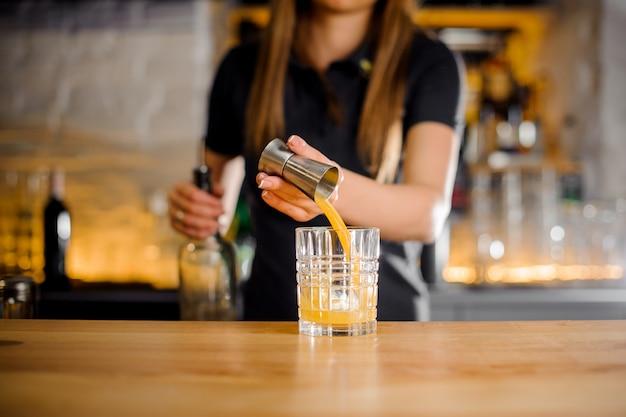 Бариста в черной рубашке готовит алкогольный коктейль с соком