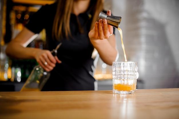 Бариста готовит коктейль и наливает апельсиновый сок в стакан