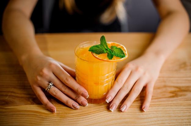 Барменша держит бокал коктейля, украшенного мятой и сушеным апельсином