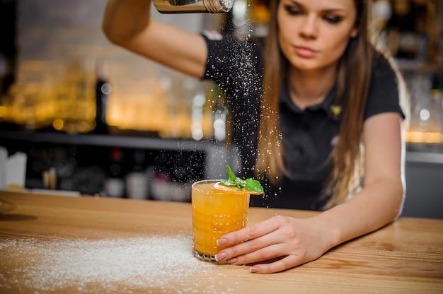 Барменша заканчивает приготовление коктейля, украшенного мятой и сушеным апельсином