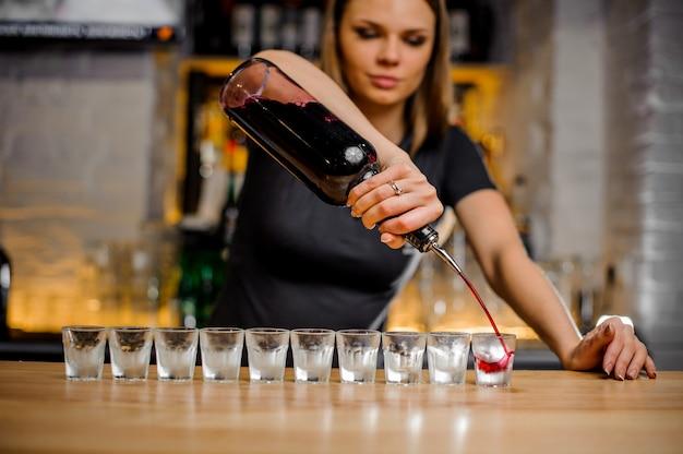 Бариста наливает малиновый спирт из бутылки в стопки