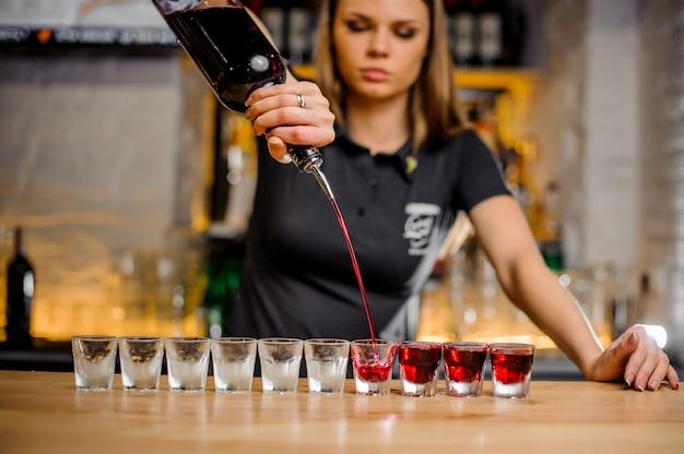Профессиональная барменша наливает алкоголь в стопки, которые выстроены в очередь