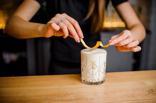 Бариста держит апельсиновую цедру над алкогольным коктейлем
