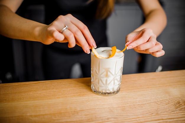Хозяйка кладет апельсиновую цедру в алкогольный коктейль с белой пеной