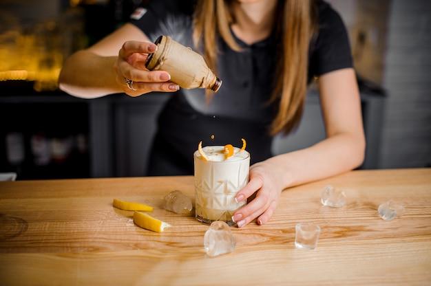 Барменша добавляет топпер в белый коктейль с апельсиновой цедрой