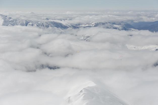 Параглайдинг в облачном голубом небе над горами