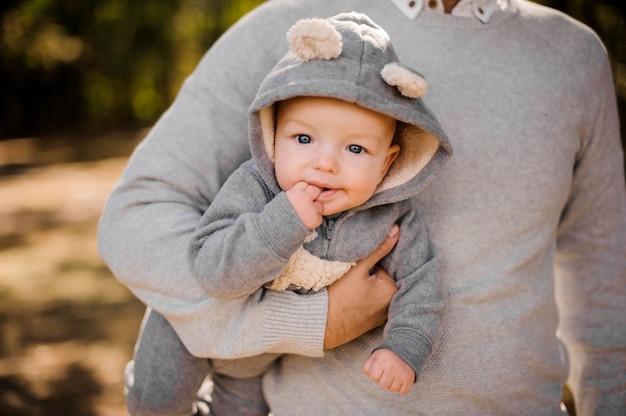 面白い子供はパパの手に柔らかい灰色のスーツで指を噛みます