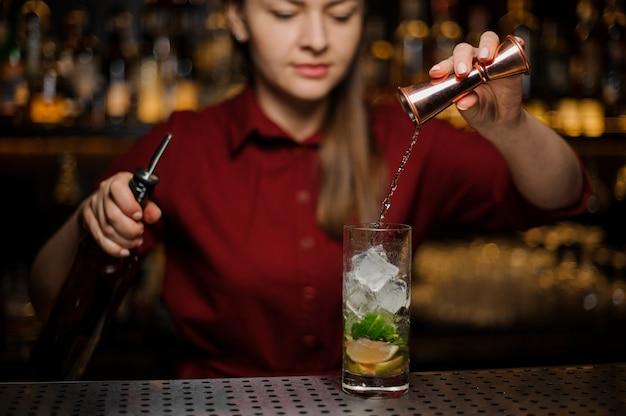 Барменша заканчивает приготовление алкогольного коктейля мохито