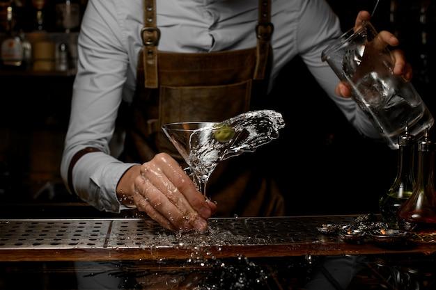 Бармен мужского пола смешивает алкогольный напиток в бокале для мартини с одной оливкой