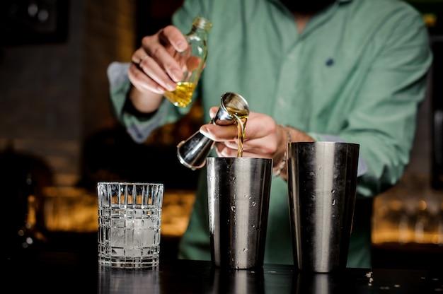 バーテンダーはバーにアルコールを注ぐ