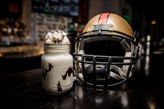 ミルクチョコレートドリンクとフットボール用ヘルメットをクローズアップ