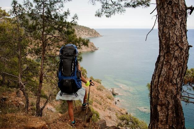 Вид сзади девушка с рюкзаком и походные палки, стоя на скале
