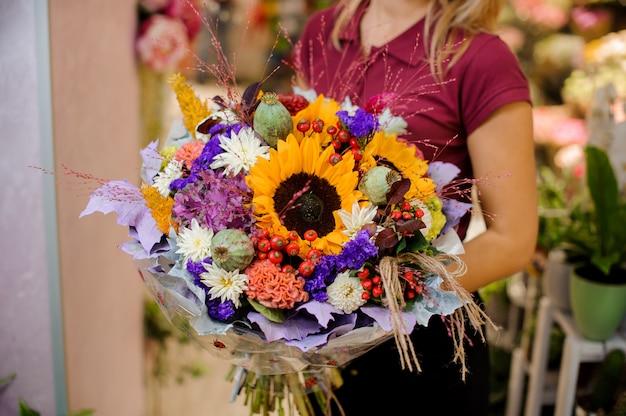 コーンフラワー、ヒマワリ、乾燥ケシ、菊、果実の花束を持って女の子