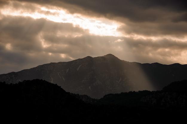 光と曇り空の下の山の美しい風景