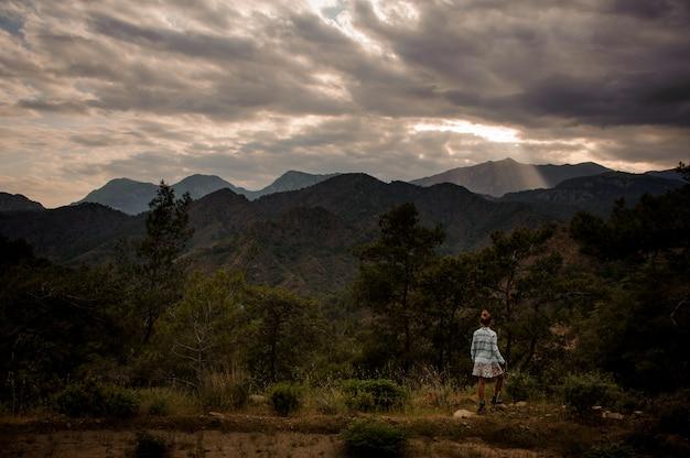 曇り空の下で山の美しい風景に立っている女の子