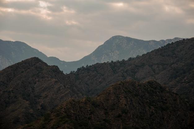 光と曇り空の下の山の風景