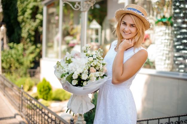 Девушка в белом платье и соломенной шляпе держит праздничный букет