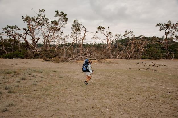 Спортивная девушка с рюкзаком и походными палками, прогуливаясь по сухому полю