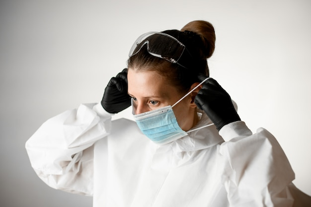 防護服と彼女の顔にマスクを置く黒い手袋の女