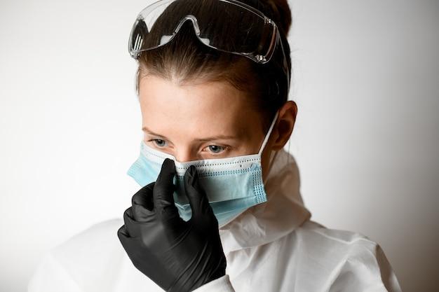 Портрет молодой женщины, которая регулирует медицинскую маску на лице