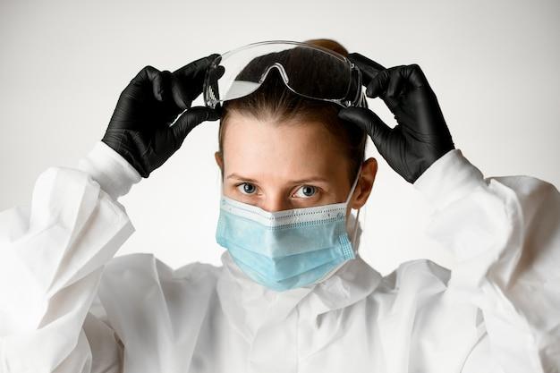 医療マスクと白い防護服の若い女性看護師が彼女の頭にゴーグルを調整します