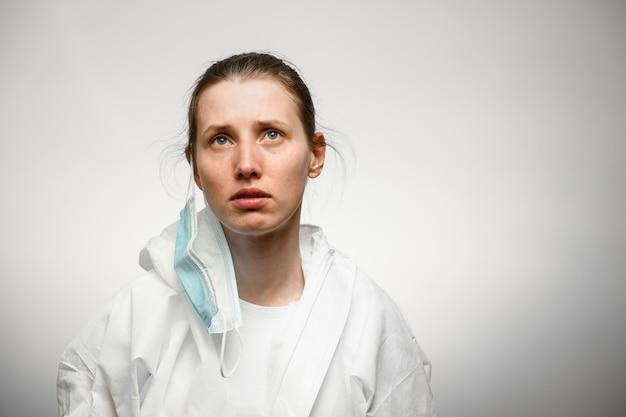 医療マスクで殉教者の顔を持つ若い女性のクローズアップ