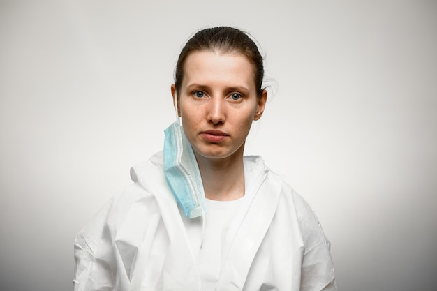 医療用マスクを外して立っている若い女性看護師