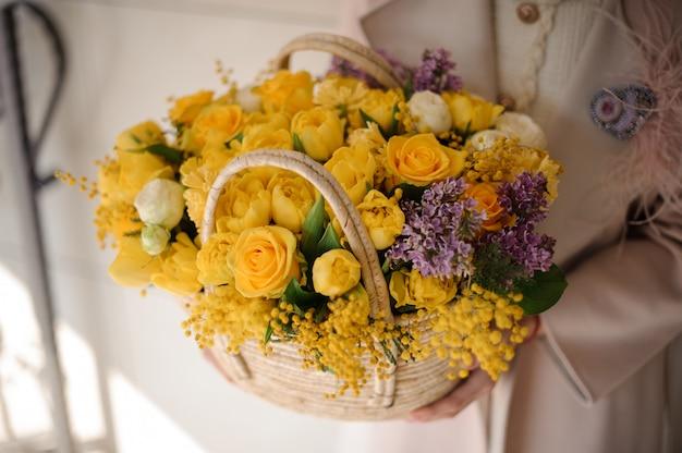 柔らかい黄色の花の春のバスケットを保持している女性