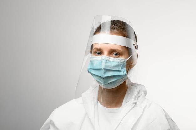 医療マスクと彼女の頭の上の保護シールドの若い女性