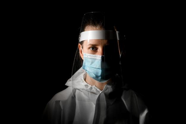 医療用マスクと暗い部屋で彼女の頭の上の保護シールドの若い女性看護師