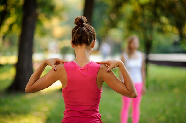 Вид сзади молодой и стройной женщины делают упражнения йоги