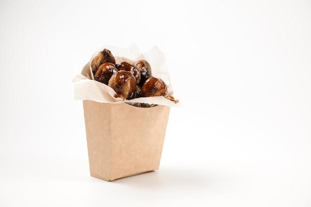Аппетитные изолированные каштаны в бумажном пакете на белом
