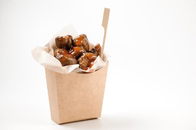 Изолированная бумажная сумка с вкусными каштанами и соусом на белом фоне