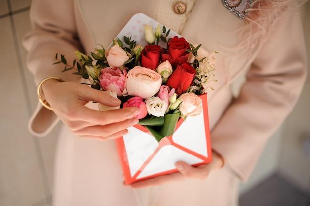 柔らかいピンクと情熱の赤い花の小さな箱を保持している女性