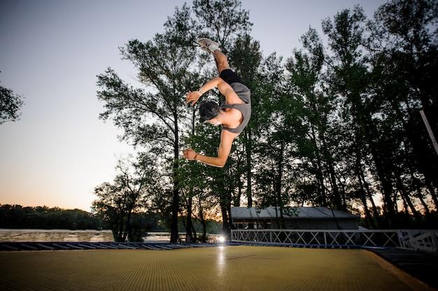 Молодой человек, одетый в повседневную одежду, прыжки на батуте в парке