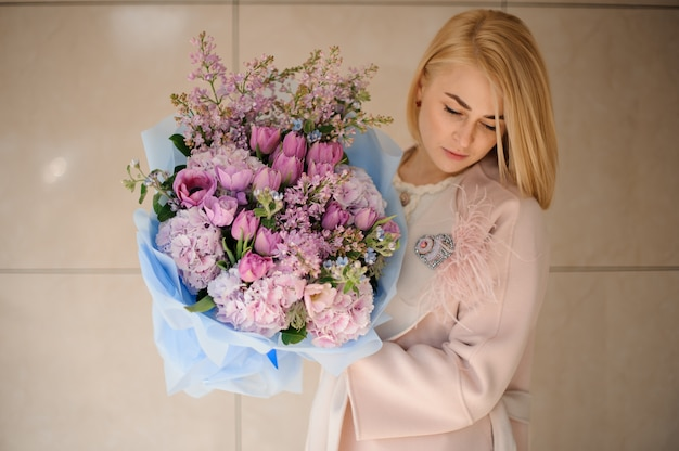 紫色の紫チューリップとライラックの花束を保持しているコートの女の子