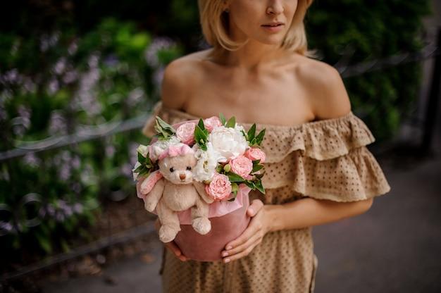 花でいっぱいのボックスを保持しているブロンドの女性
