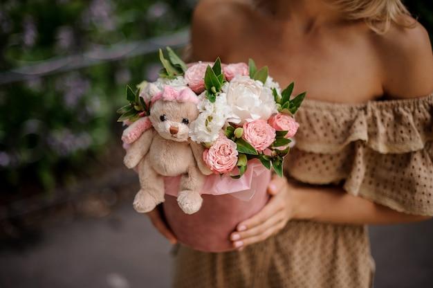 花でいっぱいの箱を持った女性