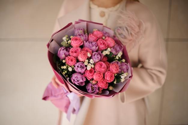 紫の紫とピンクの花の花束を保持しているコートの女性