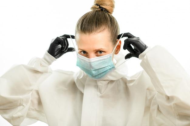 白い防護服と黒い手袋で金髪の女性がサージカルマスクを置く