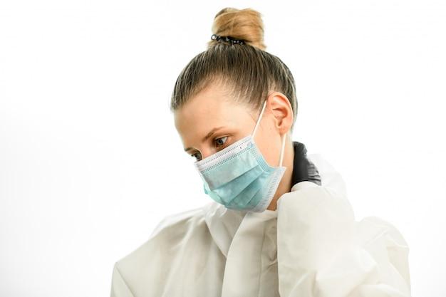 防護服の若い女性医師は彼女の首に手を握る