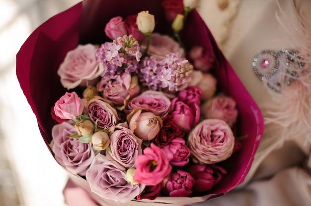 紫色の紫の花の花束を保持しているコートの女の子を閉じる