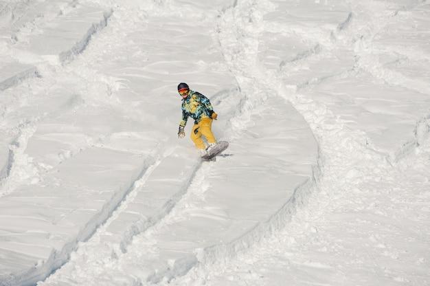 明るい冬の日に雪の丘を下って乗る明るいスポーツウェアのスノーボーダー