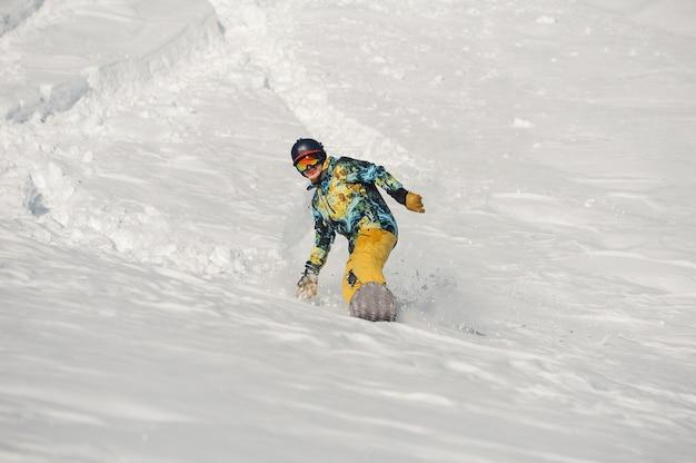 Молодой сноубордист в яркой спортивной одежде, езда по снежной горке в яркий зимний день