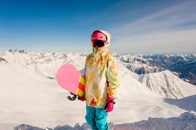 Женский сноубордист в яркой спортивной одежде стоит на вершине горы в грузии, гудаури